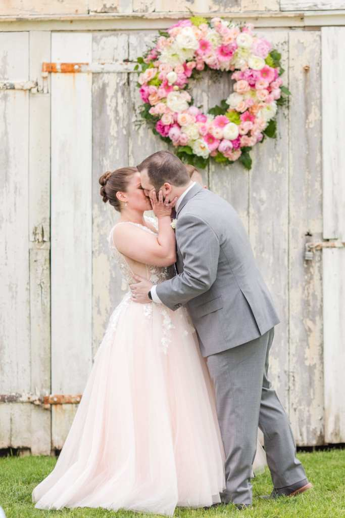 bride and groom kissing after being pronounced husband and wife in front of whitewashed barn with floral wreath of pink, blush, magenta and cream florals