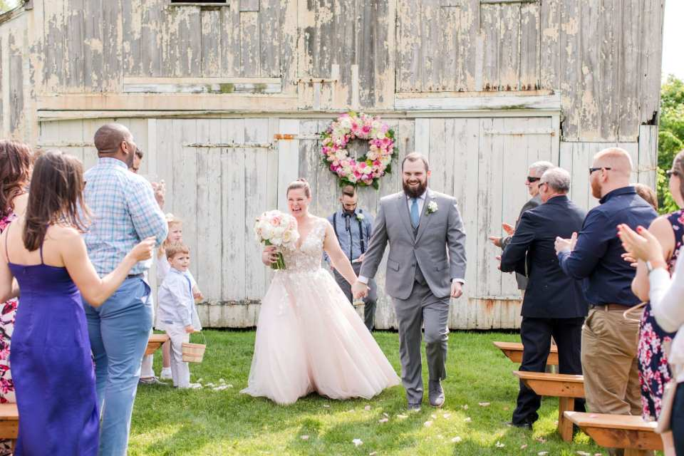bride and groom immediately after being pronounced husband and wife in the middle of the aisle, laughing and smiling