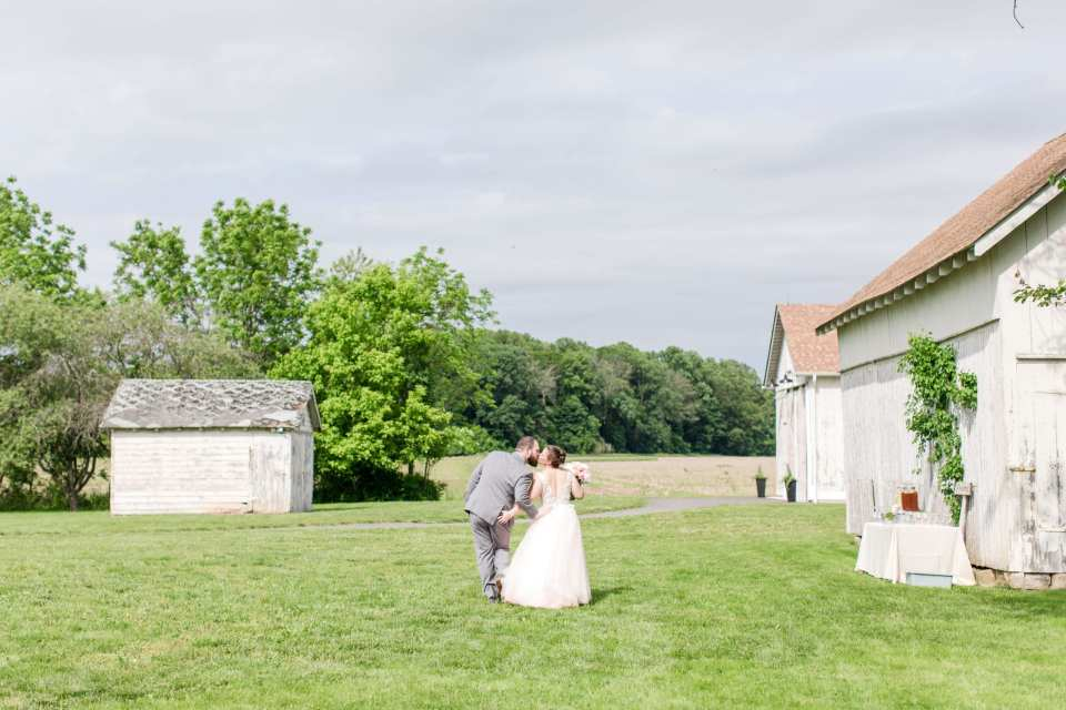 wide angle photo of the bride and groom kissing after their wedding ceremony on the farmstead