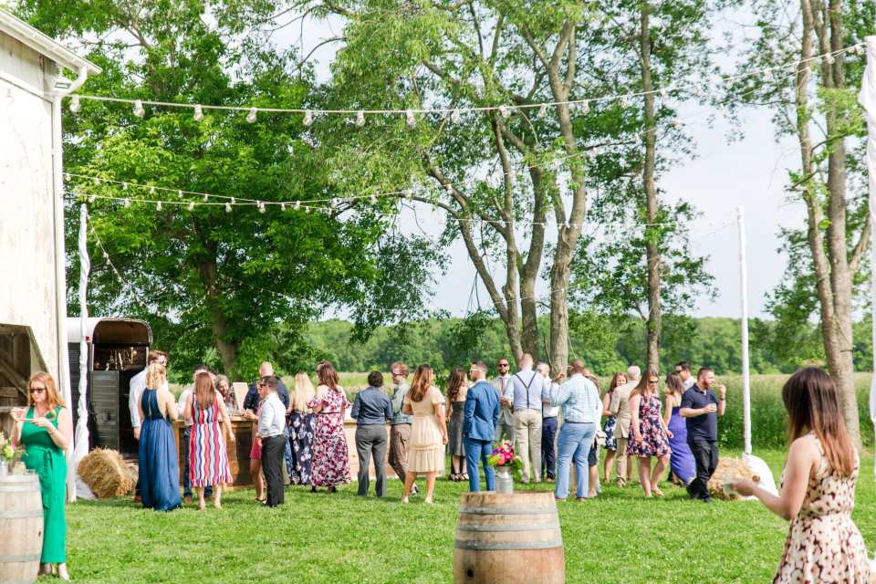 wide angle photo of outside the barn during the cocktail hour of the wedding reception featuring a line of guests at the custom wooden bar from 13th Street Cocktails