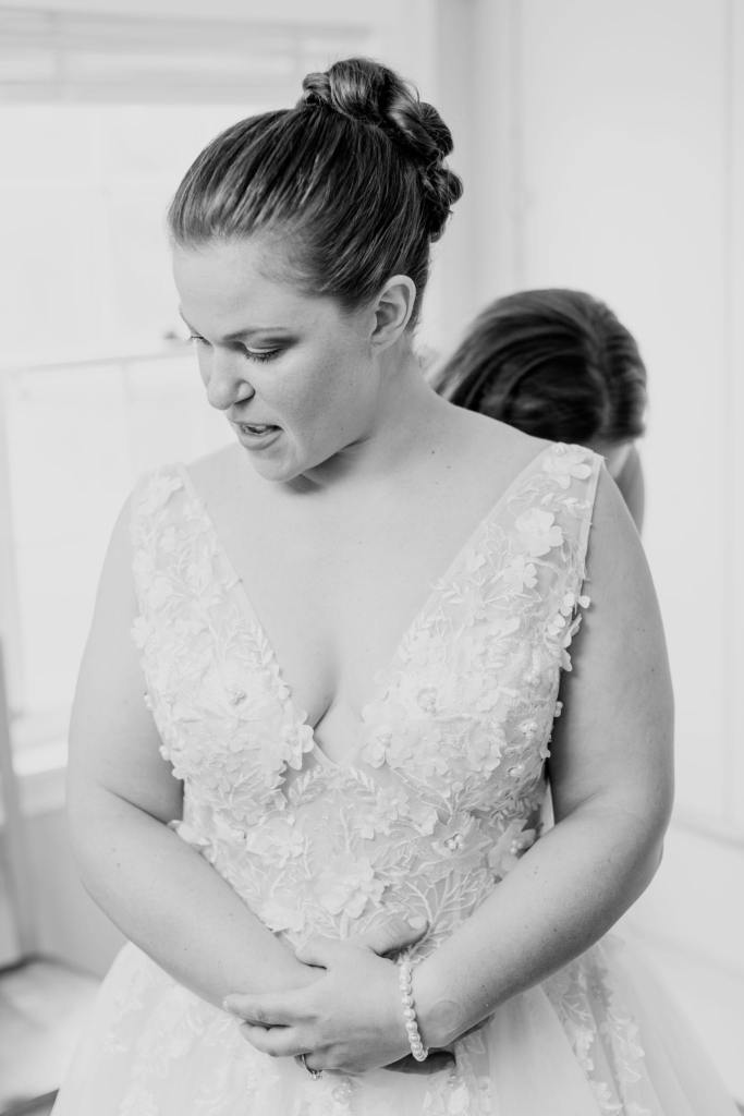 black and white photo of the bride gazing down while being buttoned into her gown