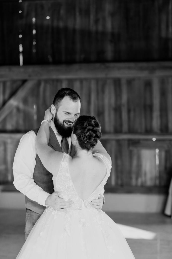 black and white photo of bride and groom during their first dance inside the barn, taken from the back of the bride, seeing the grooms smile at his bride