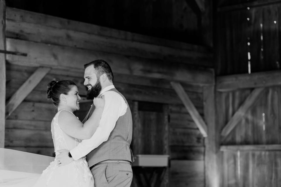 black and white wide angle shot of bride and groom inside the barn during their first dance