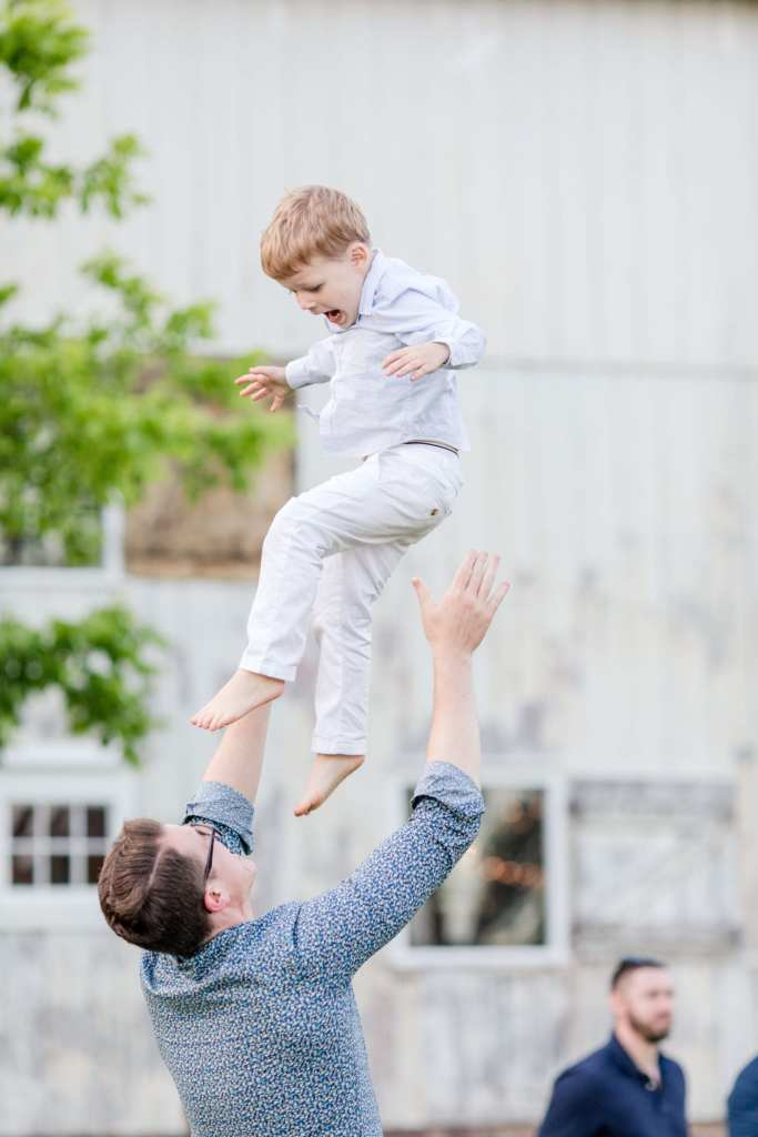 brides brother tossing his son into the air outdoors