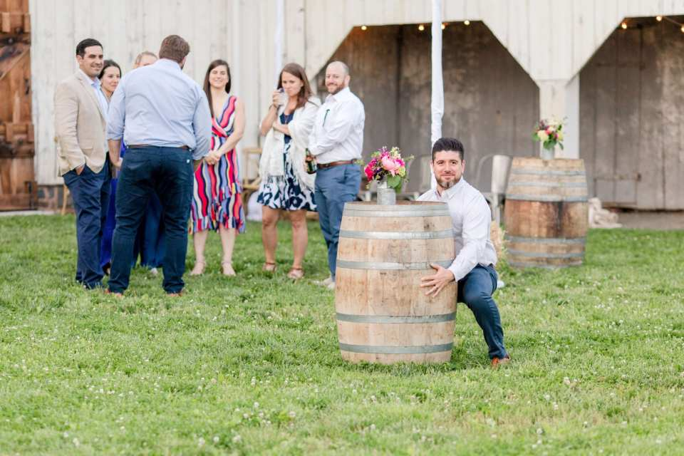 guests enjoying the outdoor area behind the barn during the cocktail hour prior to the wedding reception