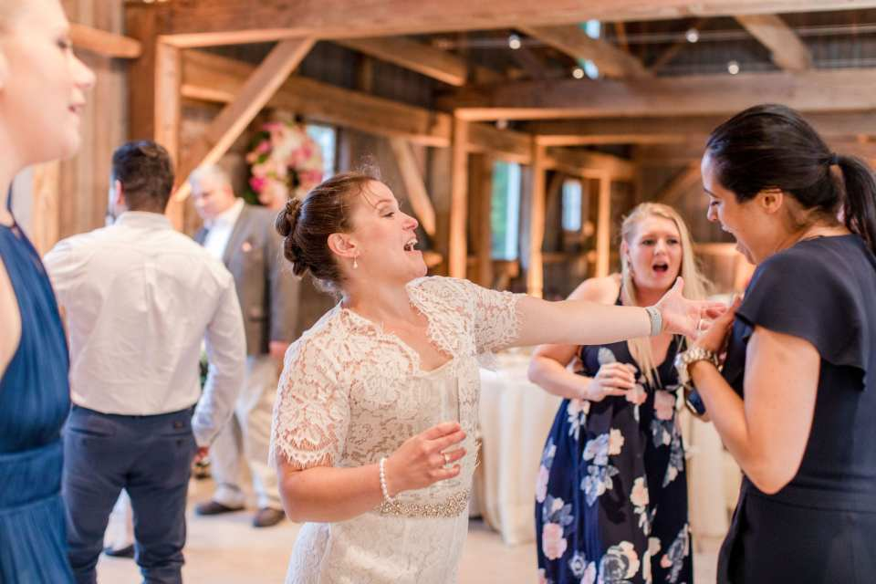 bride and guests dancing during the reception inside the barn