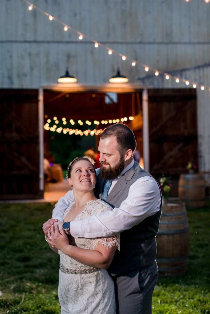 photo of bride in relaxed jumper with her groom wrapping his arms around her outside of the barn at dusk