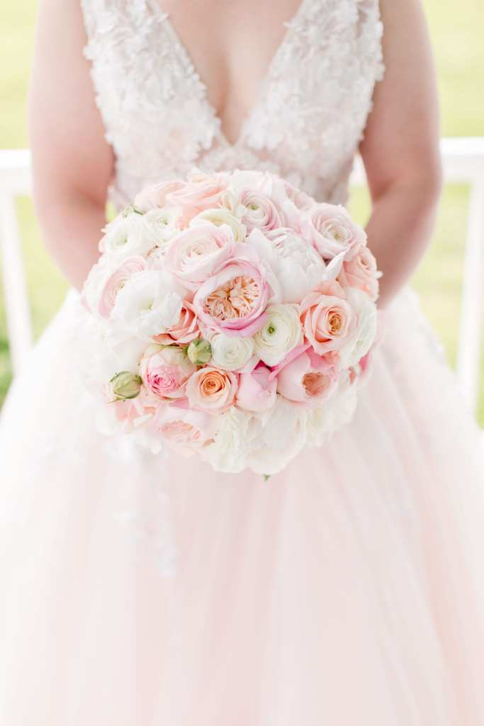 focus on the bridal bouquet held at the brides waist of white and pink florals