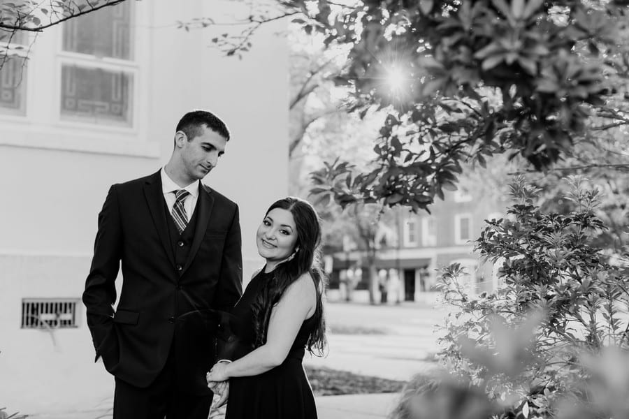 Black and white photo of the bride to be wrapping her arms around the left arm of the groom to be. He is gazing down at her, she is looking at the camera, smiling