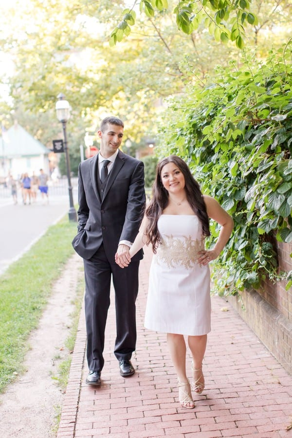 Bride to be in a white strapless short dress with gold applique at the torso by Lilly Pulitzer, gold strappy heels by Badgley Mischka leading her groom to be in a solid black 3 piece suit by Calvin Klein. On the campus of Princeton University.