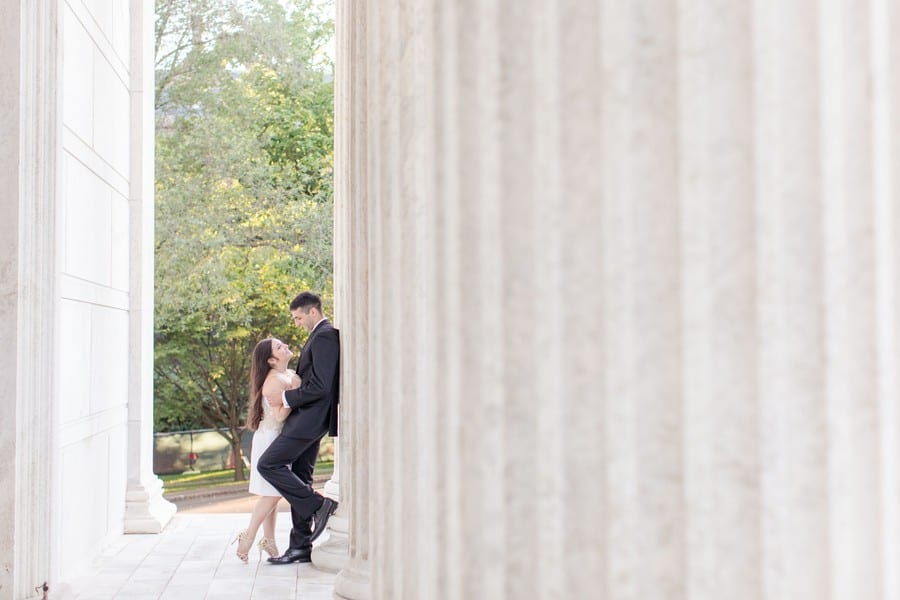 "engaged couple leaning against column of building on the campus of Princeton University. He is in a black suit, leaning against the column, left foot bent up against the colum, she is in his arms, right leg bent up ""hollywood kiss"" style. She is in a short white strapless dress with gold applique at the waist, along with gold strappy heels, long hair slightly curled and flowing down her back"