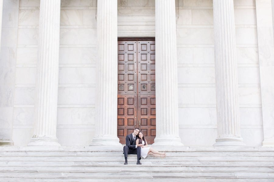 The engaged couple sitting on the steps of a large white building with large columns and two wooden doors on the campus of Princeton University. He is sitting facing the camera in a black suit with white shirt and black tie, she is leaning against him with her legs outstretced on a stair in a light colored dress