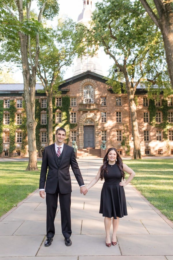 Bride to be dressed in a short black dress by Aqua, shoes by Kelly & Katie from DSW, holding hands with her groom to be, dressed in a 3 piece suit by Calvin Klein, in front of Nassau Hall at Princeton University