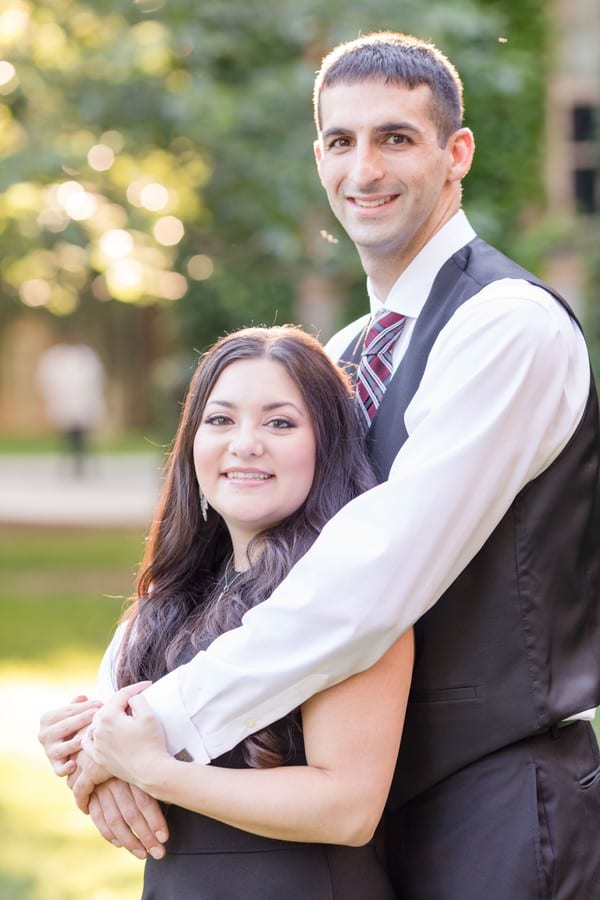 Bride to be in an Aqua black sleeveless short dress, standing in front of her groom to be, wrapped in his arms, both looking at the camera, smiling. He is dressed in a black Calvin Klein 3 piece suit, without the suit jacket