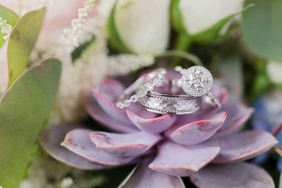 A close up photo of the brides round diamond engagement ring with diamond alo, her antique style wedding band, along with the grooms hammered white gold wedding band on a purple succulent flower