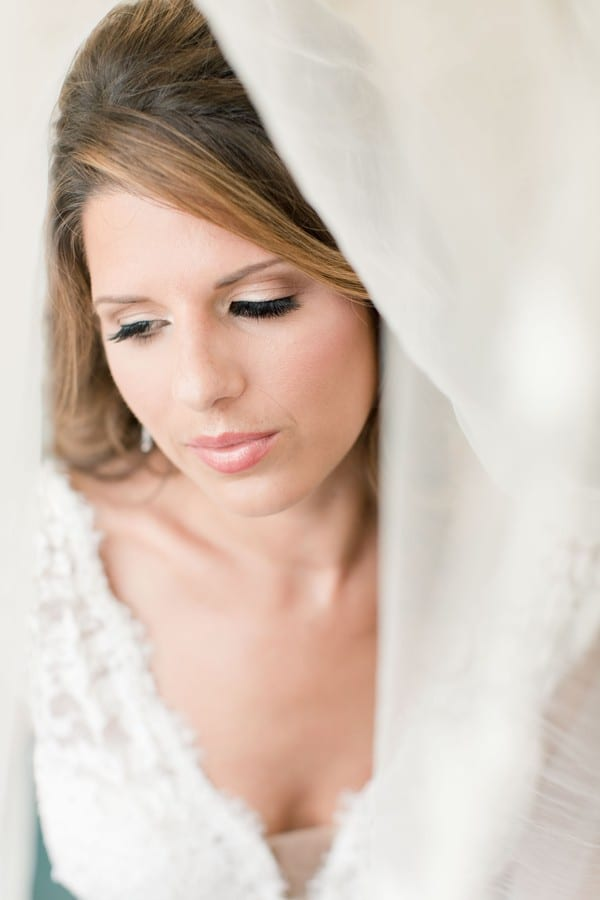 bridal portrait of the bride looking down away from the camera, from under her veil. Makeup by Michelle Renee Beauty
