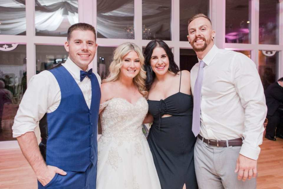 Bride and groom pose with two guests whom caught the bouquet and garter during the reception at Skyview Golf Club