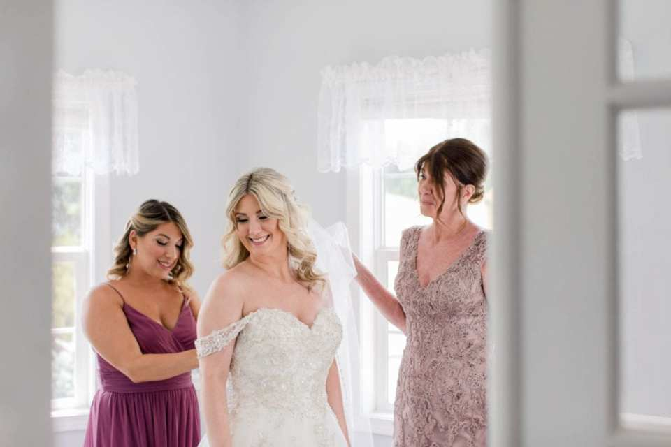 Bride being put into her gown by her maid of honor and mother