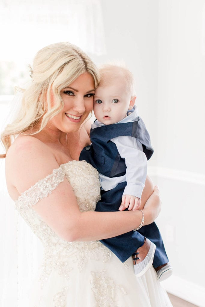 Bride smiling while holding a baby boy