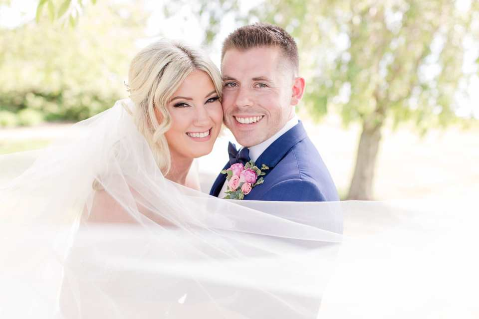 Close up of the faces of the bride and groom, veil flowing in front of them while they smile