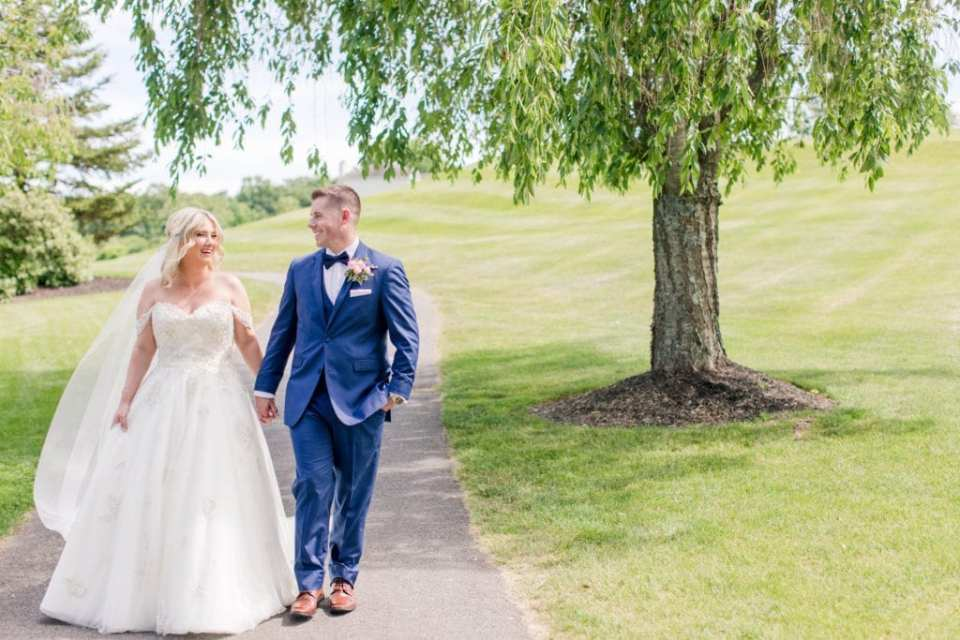 Bride and groom strolling hand in hand on a golf cart pathway through Skyview Golf Club course