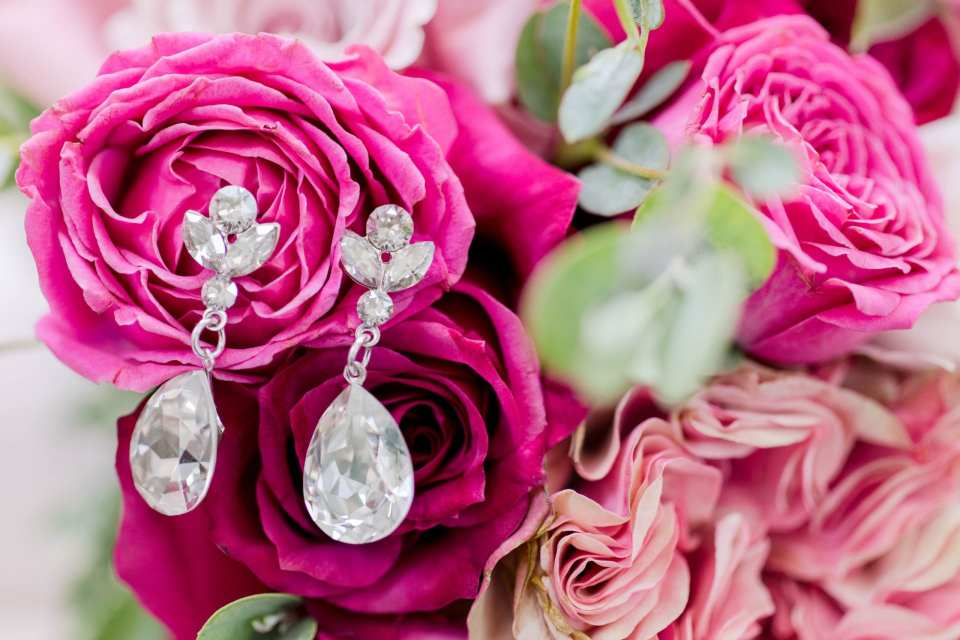 the brides drop earrings on pink roses in her bouquet