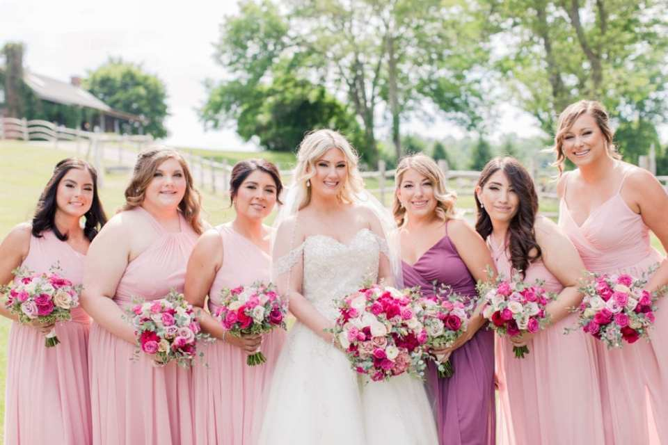 formal photo of the bride in Justin Alexander with her bridal party in pink gowns by David's Bridal