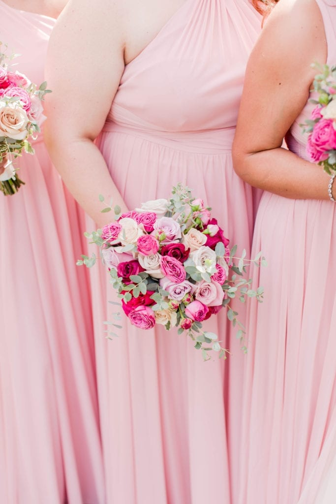 3/4 photo of bridesmaids in light pink gowns by David's Bridal holding their bouquets of pink florals in varying shades, along with white florals and greenery by Pink Dahlia Events