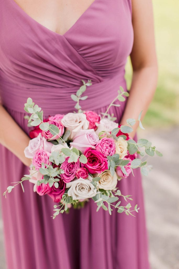 focus on a member of the bridal party in a dark pink gown by David's Bridal holding a bouquet of various pink florals by Pink Dahlia Events