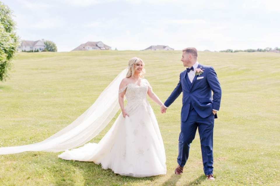 the groom leading the bride by the hand down the Skyview Golf Club course. Gown by Justin Alexander, navy blue tuxedo by the Clothing Center
