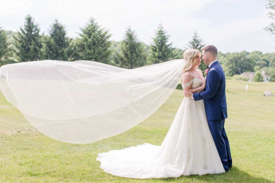 side view portrait of the groom holding the bride at her waistline, veil floating in the air, with the Skyview Golf Course in the background