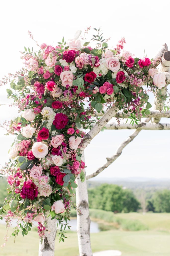 The florals decorating the ceremony altar area in various shades of pinks and white, along with greenery by Pink Dahlia Events.