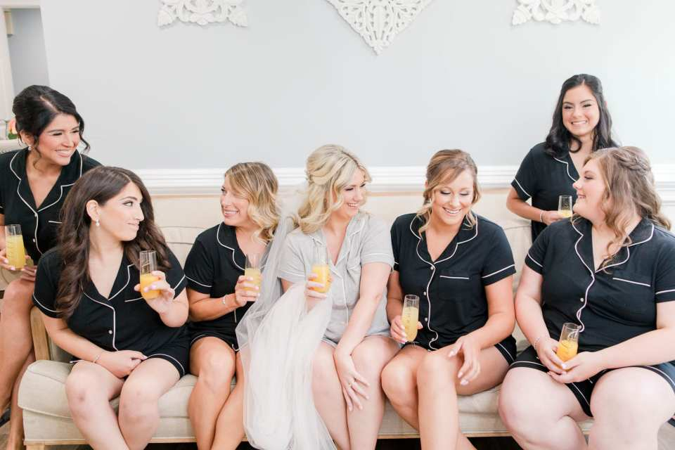 the Bride in grey pajamas, holding a mimosa, surrounded by her bridal party in black pajamas, also holding mimosas