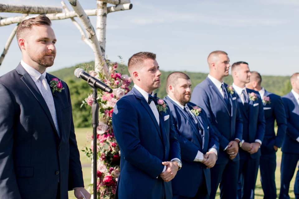 The officiant next to the groom, who is next to his groomsmen looking on as the bride walks down the aisle.