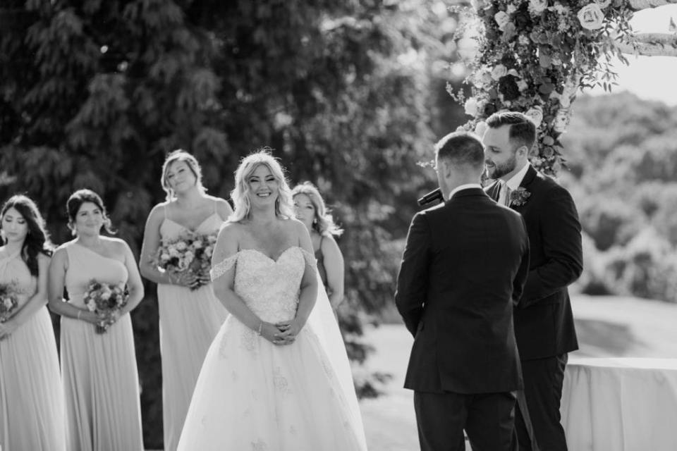 black and white photo of the bride smiling as the ceremony goes on, bridal party looking on in the background