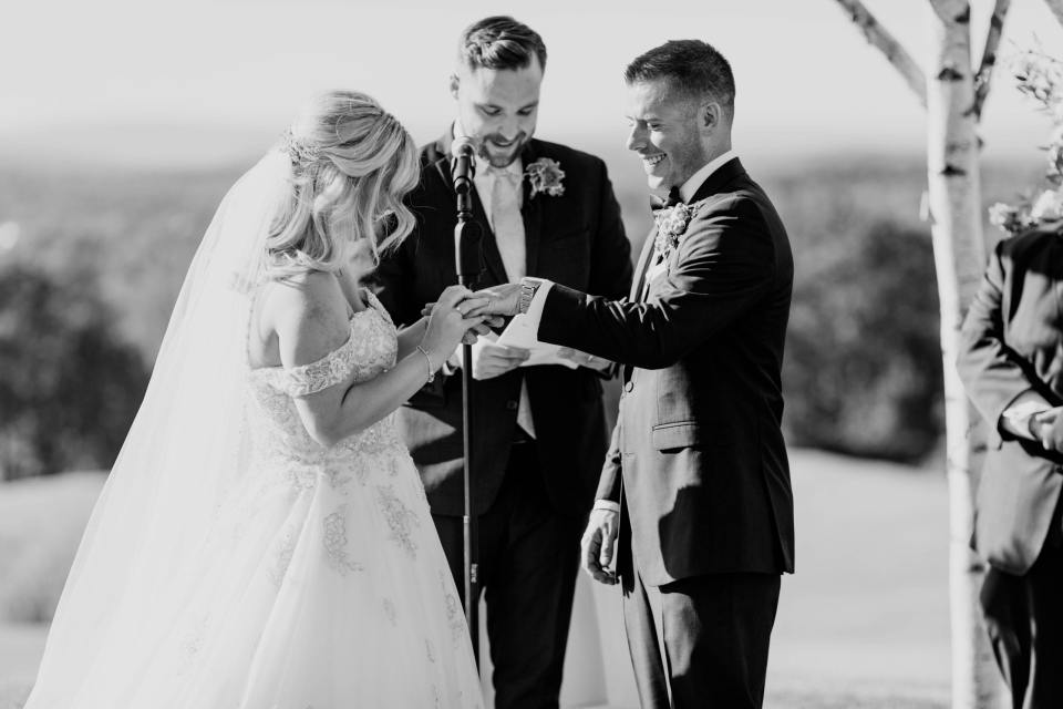 black and white photo of the bride placing the wedding ring on her new husbands finger during the ceremony