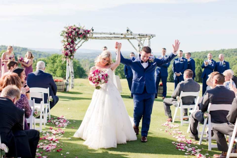 Bride and groom raise their arms in joy as they walk down the aisle after being pronounced husband and wife. Birchwood and floral archway and tree covered mountains in the background at the Skyview Golf Club