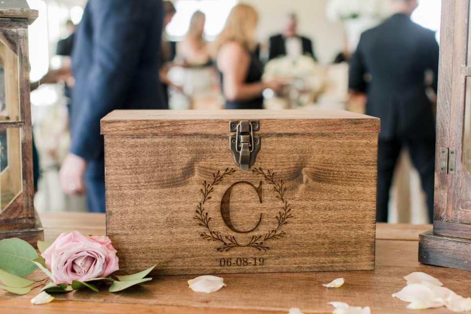 "a photo of the wooden card box with a ""C"" carved into it along with the date of the wedding"