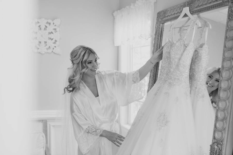 Black and white photo of the bride in a white silk robe admiring her gown by Justin Alexander, hanging on a mirror
