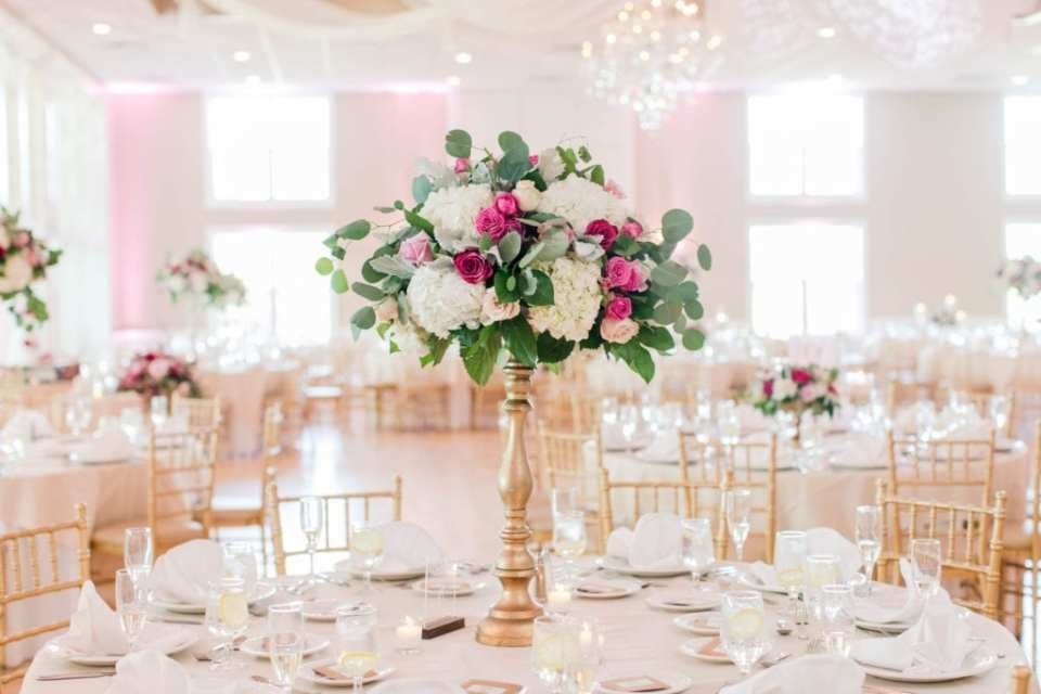 a tall floral arrangement of greenery and florals in shades of pink and white atop a gold pedestal by Pink Dahlia Floral Design, surrounded by white votive candles