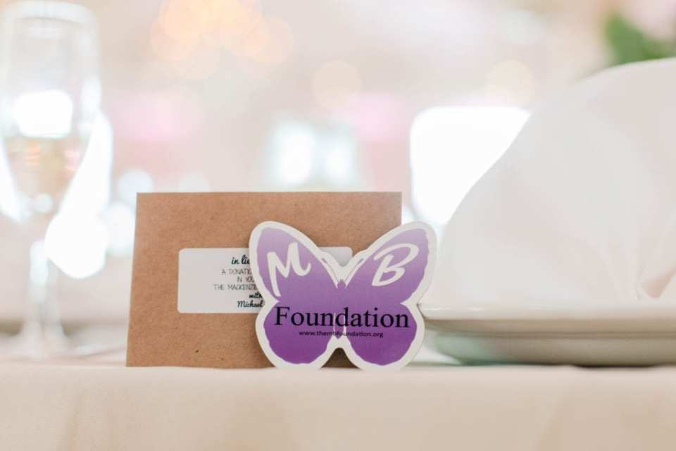 photo of a purple butterfly card in front of a brown cardstock card indicating that in lieu of favors, a donation was made to the charity of the bride and groom's choice