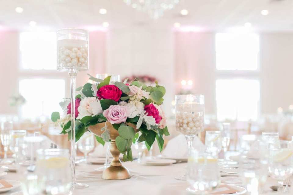 a low floral arrangement of greenery and florals in shades of pink and white in a gold urn by Pink Dahlia Floral Design, surrounded by white floating candles of varying heights