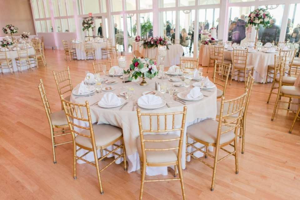 a wide photo of the reception area at the Skyview Golf Club showing a table with a low floral arrangement, white linens and gold chivari chairs