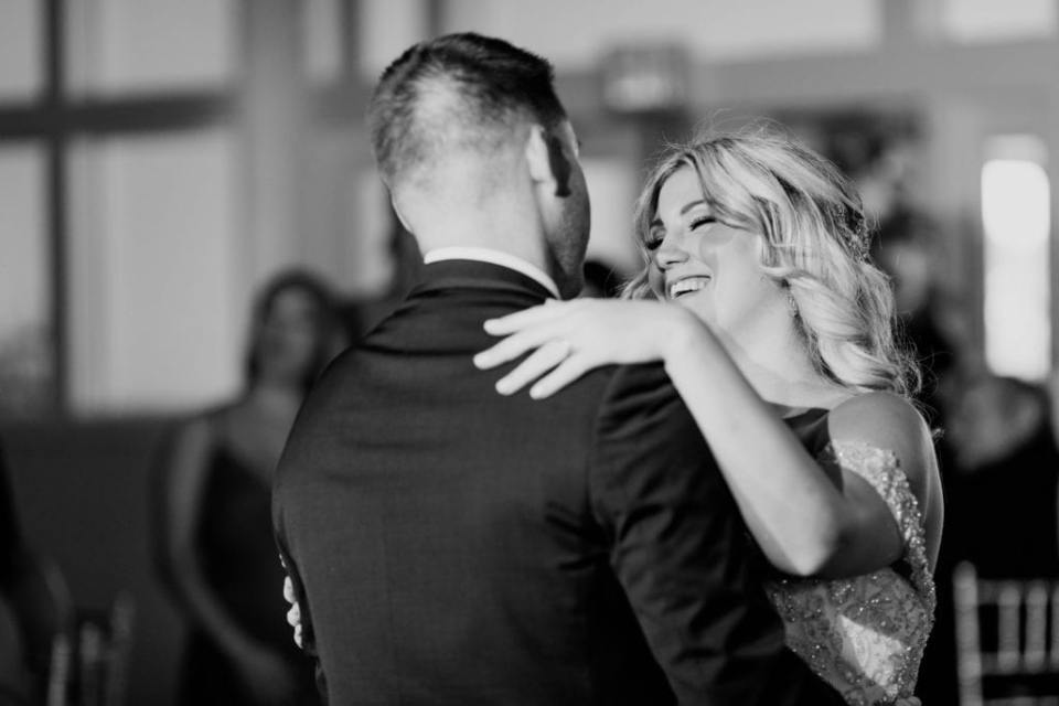 black and white candid photo of the bride smiling while dancing with her groom during their first dance