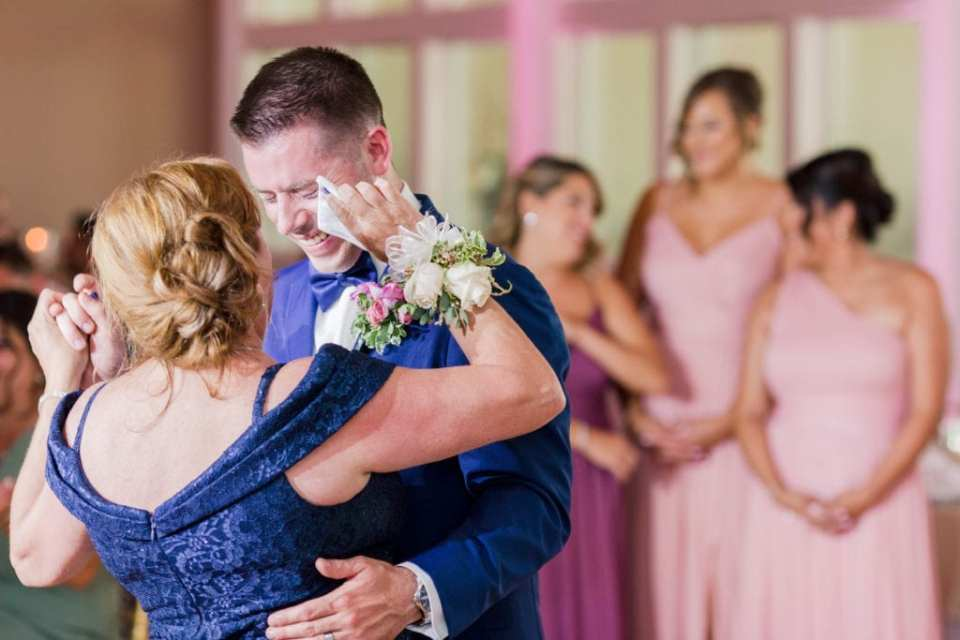 the groom dancing with his mother, during which he is shedding tears and his mother is wiping them away with a handkerchief
