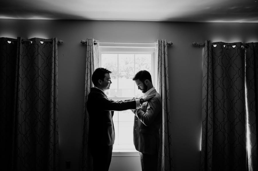 black and white candid photo of the groom being helped with his suit by a groomsman