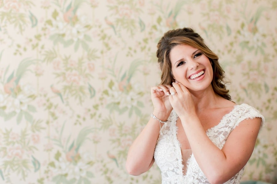 the bride smiling while putting on her earrings