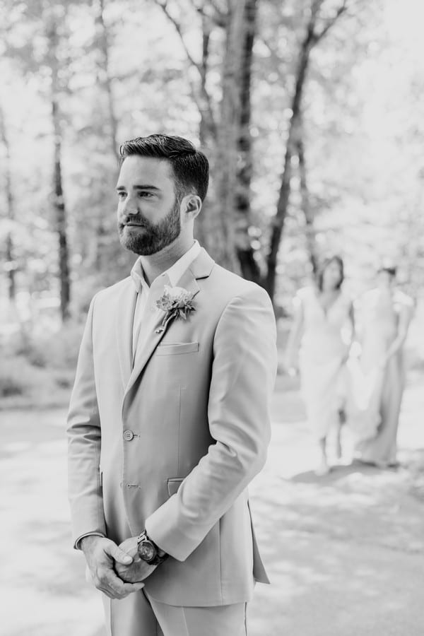 Black and white photo of the groom patiently waiting for his bride to see her during their first look. You can see her in the distance coming towards him.