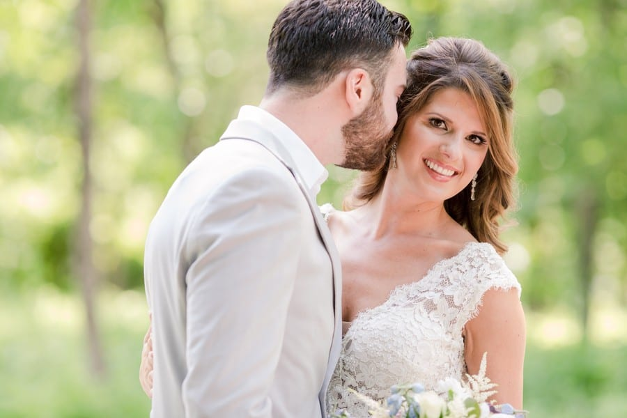bride turning toward camera smiling, while groom nuzzles the side of her head