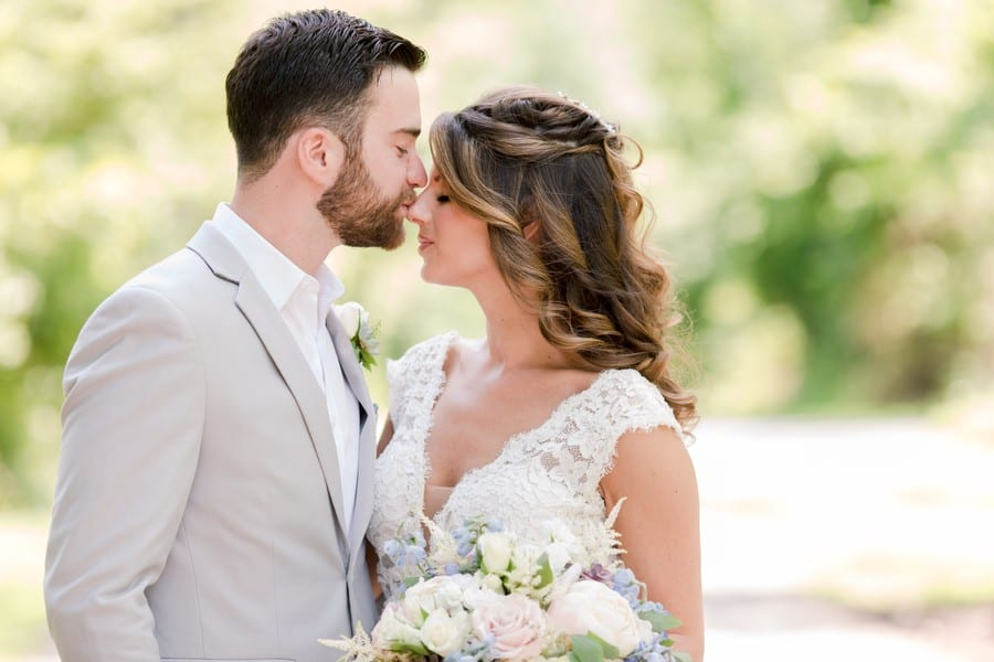 Close up of groom kissing the nose of the bride, both of their eyes closed. Her hair by Kara Russell